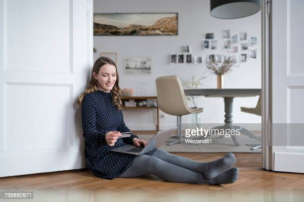 Smiling woman at home sitting on floor with laptop in door frame holding credit card