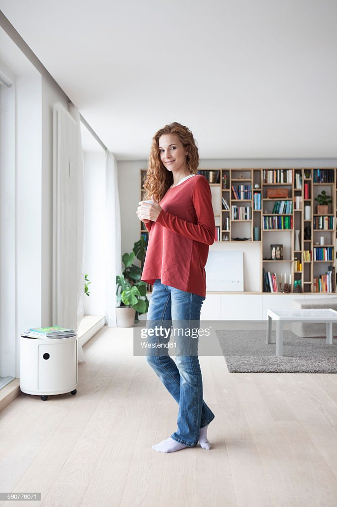 Smiling woman at home standing at the window : Stock Photo