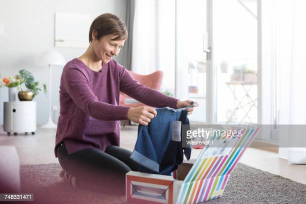 Smiling woman at home unpacking parcel with garment