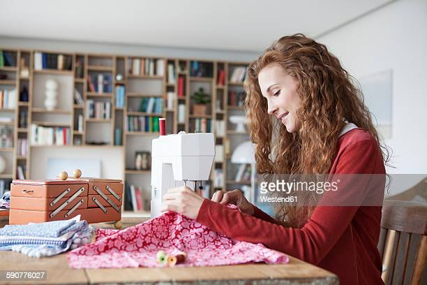 Smiling woman at home using sewing machine