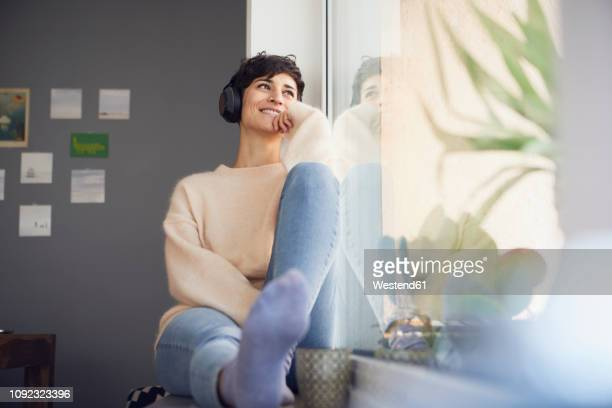 smiling woman at home wearing headphones  sitting at the window - musik stock-fotos und bilder