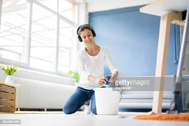 smiling woman at home wearing headphones wiping the floor - daily bucket stock pictures, royalty-free photos & images