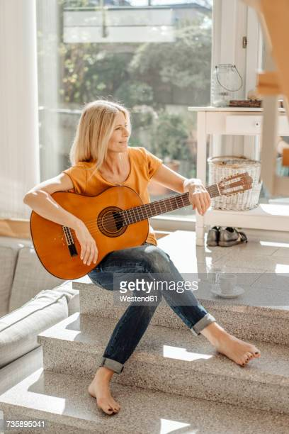 Smiling woman at home with guitar