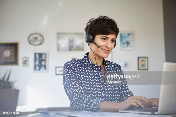 smiling woman at home with headset using laptop - video conference stock pictures, royalty-free photos & images