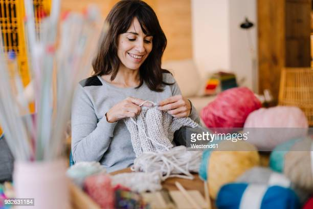 smiling woman at table knitting - knitting stock photos and pictures