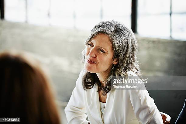 smiling woman at table with friends during party - mid length hair stock pictures, royalty-free photos & images