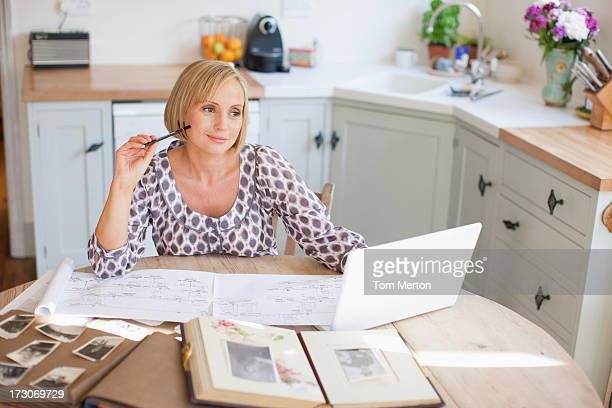 Smiling woman at table with old photographs and genealogical tree
