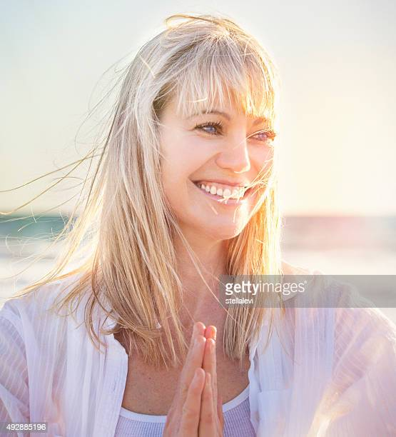 smiling woman at the beach doing yoga