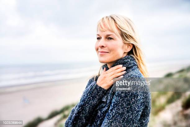 smiling woman at the sea - blond frauen strand stock-fotos und bilder