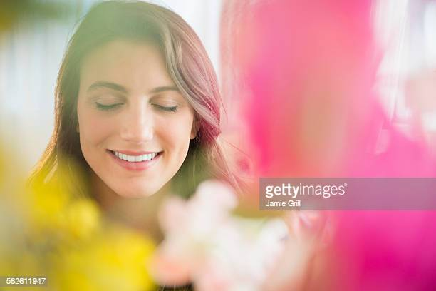 Smiling woman behind blurred flowers