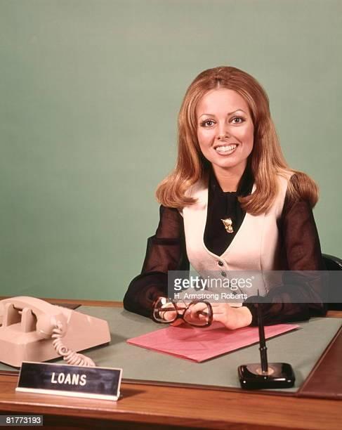 smiling woman behind desk business woman secretary receptionist bank loan officer. - 1970年 ストックフォトと画像