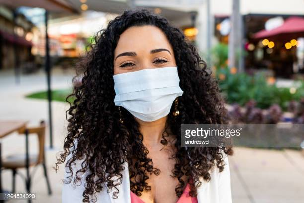 smiling woman behind face protection mask - coronavirus mask stock pictures, royalty-free photos & images