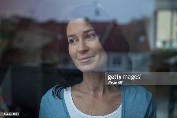 Smiling woman behind windowpane looking out