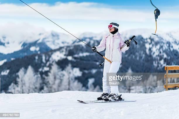 Donna sorridente essere tirato da skilift su una montagna.