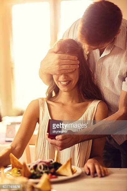 Smiling woman being surprised by her boyfriend with jewerly box.
