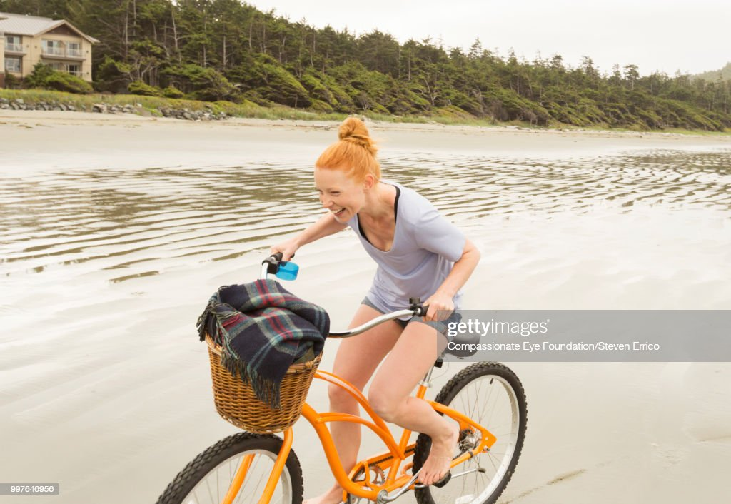 Smiling woman bike riding on beach : Stock Photo