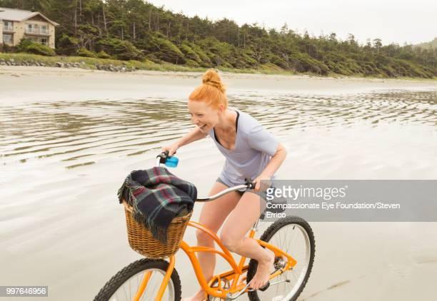 Smiling woman bike riding on beach