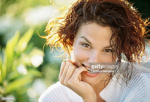 smiling woman biting finger with wet skin and hair - une seule femme d'âge moyen photos et images de collection
