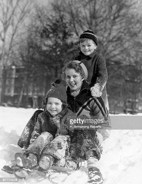 smiling woman, boy and girl standing on a sled in winter. - tobogganing stock pictures, royalty-free photos & images