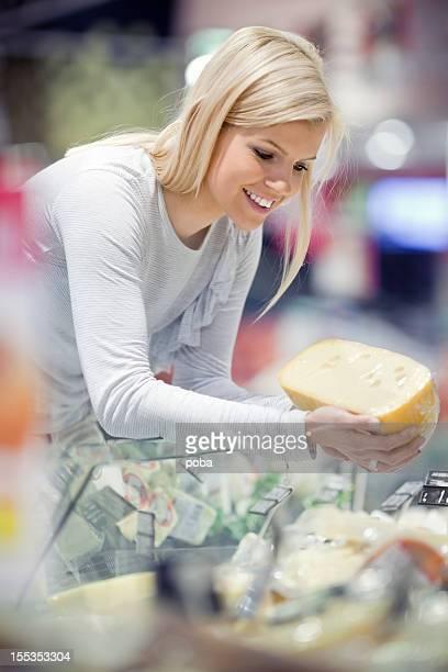 Lächelnde Frau Käse im Supermarkt kaufen