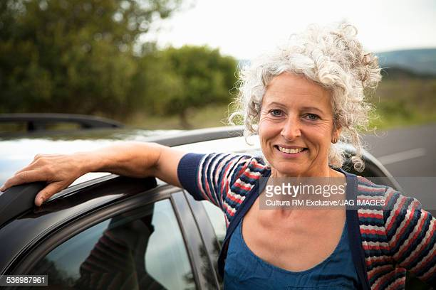 Smiling woman by car
