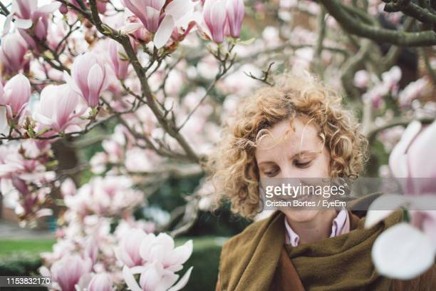 smiling woman by flowers on branches - bortes imagens e fotografias de stock