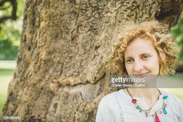 Smiling Woman By Tree Trunk