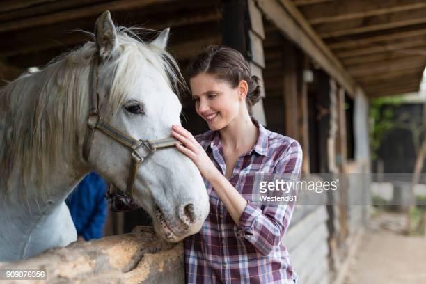 smiling woman caring for a horse on a farm - 1 woman 1 horse fotografías e imágenes de stock