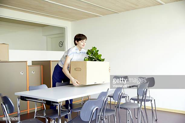 Smiling woman carrying cardboard box in new office