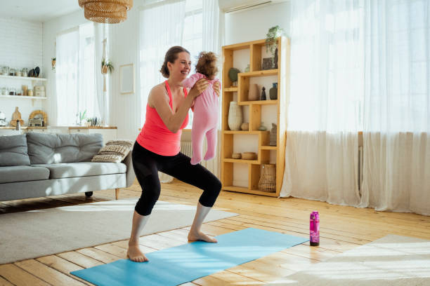Smiling woman carrying daughter while exercising in living room at home