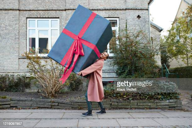 smiling woman carrying large gift box on footpath - gift stock pictures, royalty-free photos & images