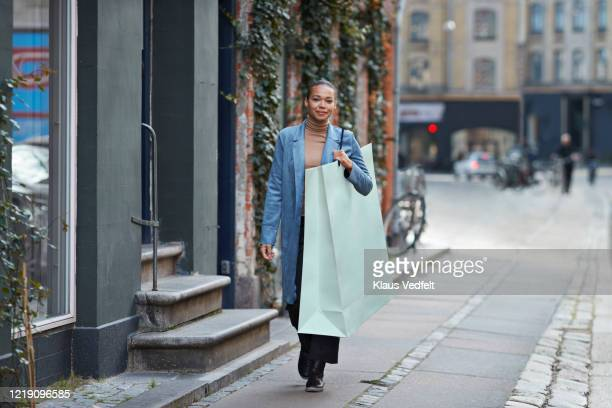 smiling woman carrying large shopping bag while walking on footpath - large stock pictures, royalty-free photos & images