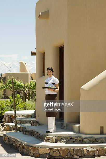 Smiling woman carrying tray with wine, Mendoza, Argentina