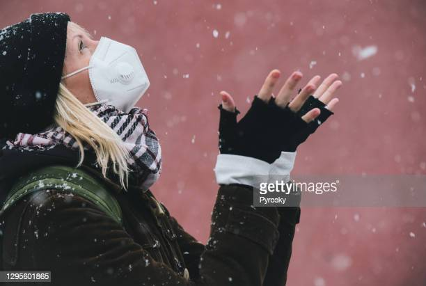 smiling woman catching snowflakes on the walk - fingerless gloves stock pictures, royalty-free photos & images