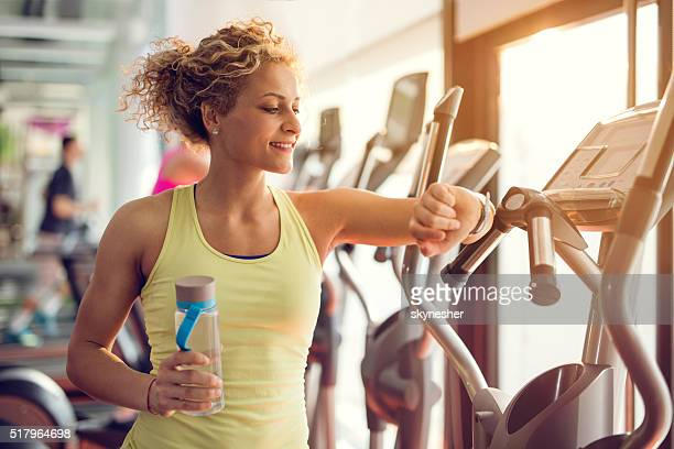 Smiling woman checking time on wristwatch in a gym.