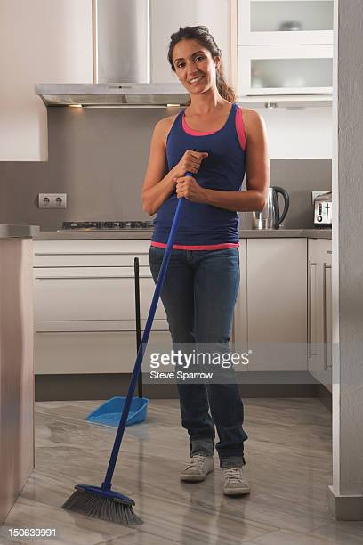smiling woman cleaning kitchen floor - sweeping stock pictures, royalty-free photos & images