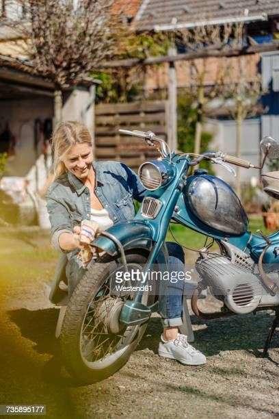 Smiling woman cleaning vintage motorcycle