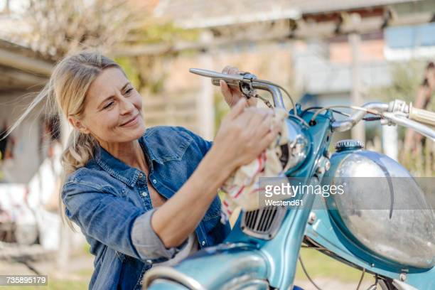smiling woman cleaning vintage motorcycle - freizeit stock-fotos und bilder