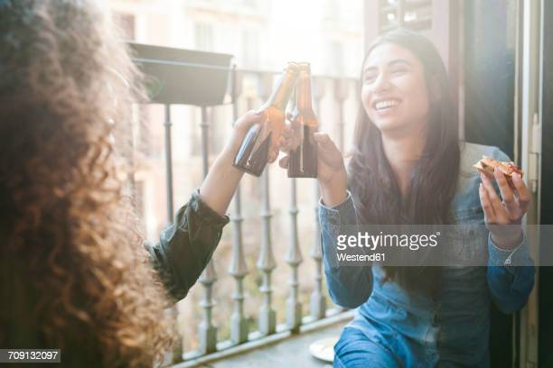 Smiling woman clinking beer bottle with her friend