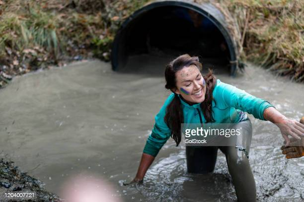 smiling woman coming climbing out of muddy pool - caucasian appearance stock pictures, royalty-free photos & images