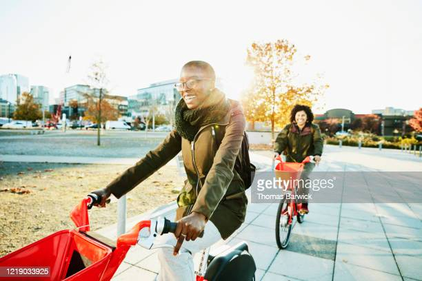 smiling woman commuting to work on electric bike share bike - sharing economy stock pictures, royalty-free photos & images