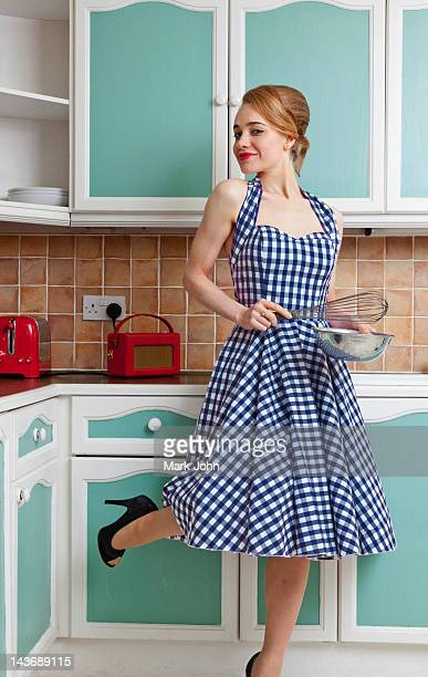smiling woman cooking in kitchen - female whipping stock-fotos und bilder