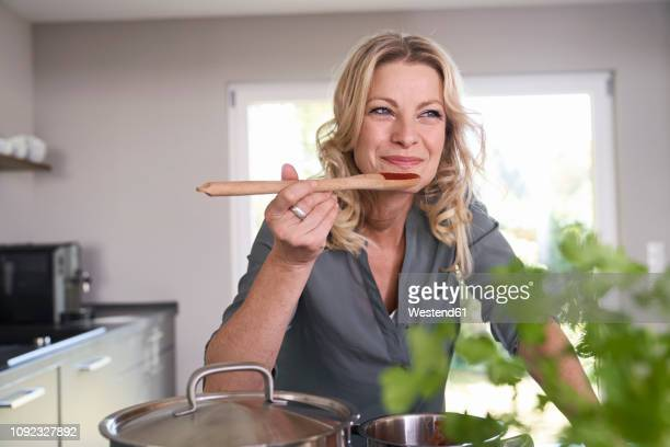 smiling woman cooking in kitchen tasting tomato sauce - tasting stock pictures, royalty-free photos & images
