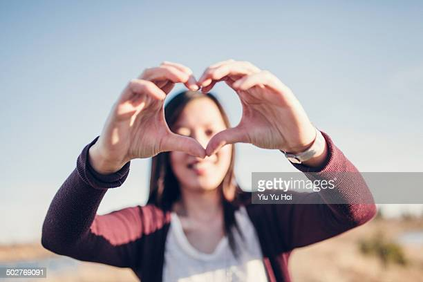 A smiling woman create a heart shape by hands