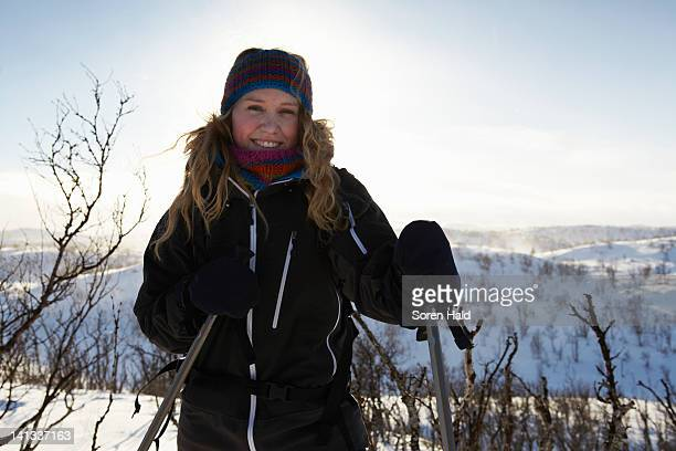 smiling woman cross-country skiing - langlaufen stockfoto's en -beelden