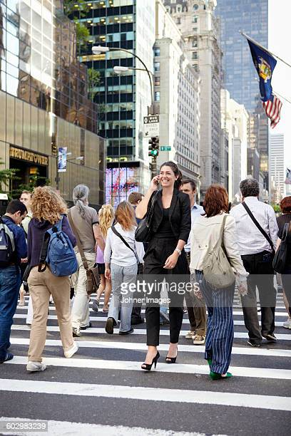 Smiling woman crossing road