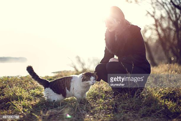Smiling woman cuddling cat in nature.