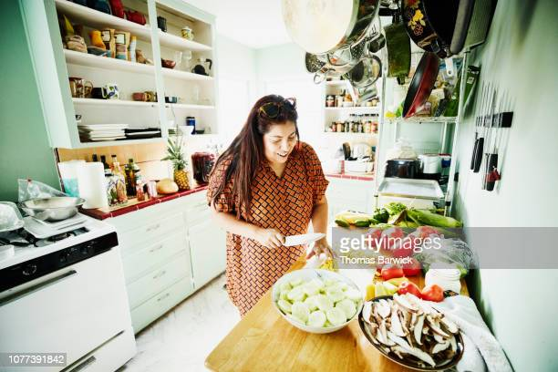 smiling woman cutting vegetables in kitchen while preparing food for party - mulheres de idade mediana - fotografias e filmes do acervo