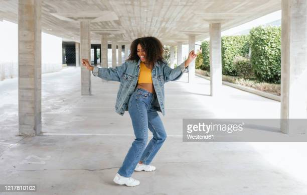 smiling woman dancing in an empty parking - jeans stock pictures, royalty-free photos & images