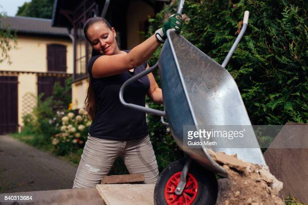 smiling woman disposing old plaster. - wheelbarrow stock photos and pictures